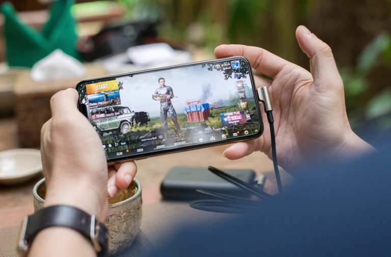 Person holding mobile phone playing PUBG Mobile for Top Grossing Mobile Games in 2020 Blog Post